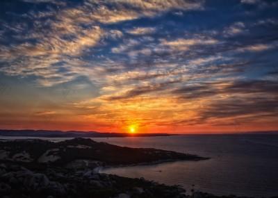 Cala di Trana beach, silky clouds and a breathtaking sunset on the North coast of Sardinia overlooking the Bocche di Bonifacio