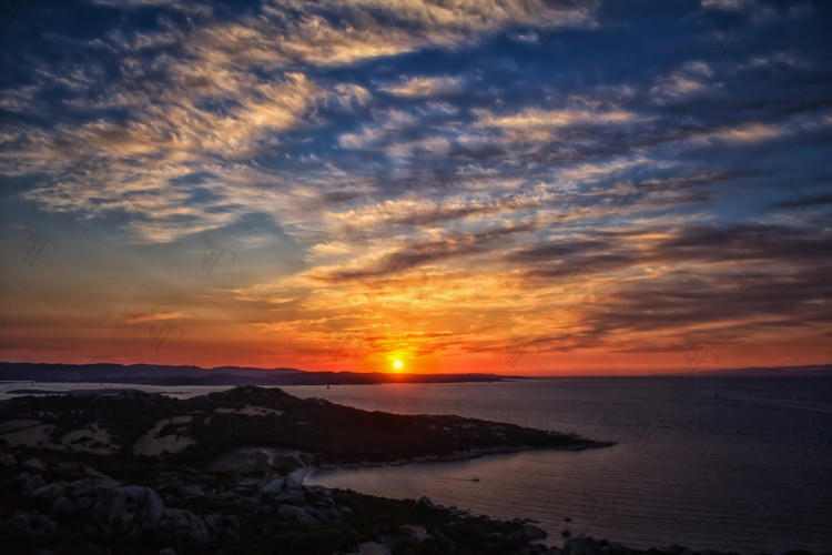 Cala di Trana beach, silky clouds and a breathtaking sunset on the North coast of Sardinia overlooking the Bocche di Bonifacio
