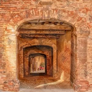 Red Vespa parked in an alley of the historic Italian village of Città della Pieve