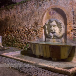 "Marble fountain in front of the church of Santa Sabina in Rome. On the left, the typical Roman cast iron fountain called ""nasone"" as it reminds a big nose."