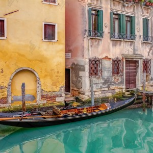 Gondola moored on the dock in a canal in Venice during the lunch break